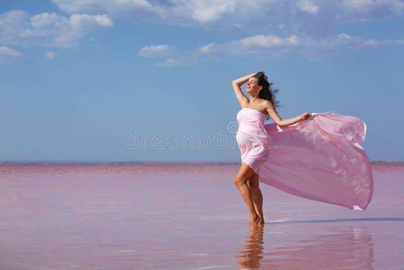Mooie jonge zwangere vrouw die van de zon op het strand, roze meer genieten stock afbeelding