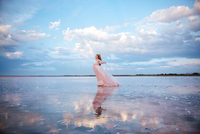 Mooie jonge zwangere vrouw die van de zon op roze meer genieten stock fotografie
