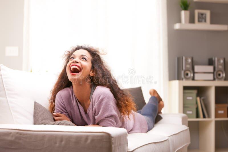 Mooie jonge zwarte gelukkige vrouw op een bank stock foto