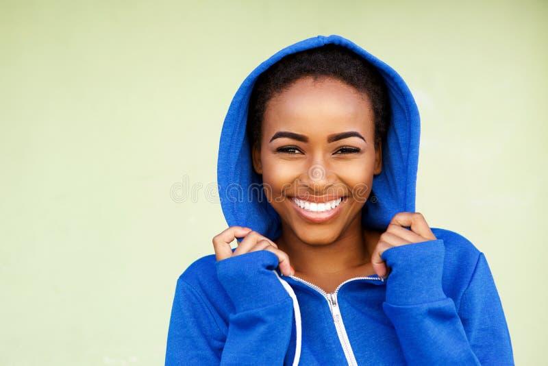 Mooie jonge zwarte maniervrouw die tegen groene muur glimlachen stock foto's