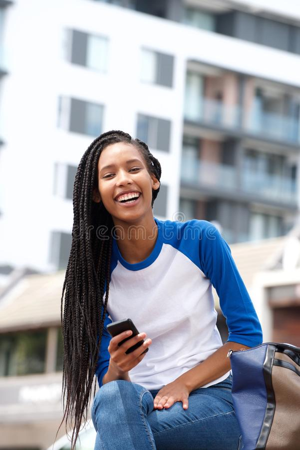 Mooie jonge zwartezitting in openlucht met cellphone en het glimlachen stock foto's