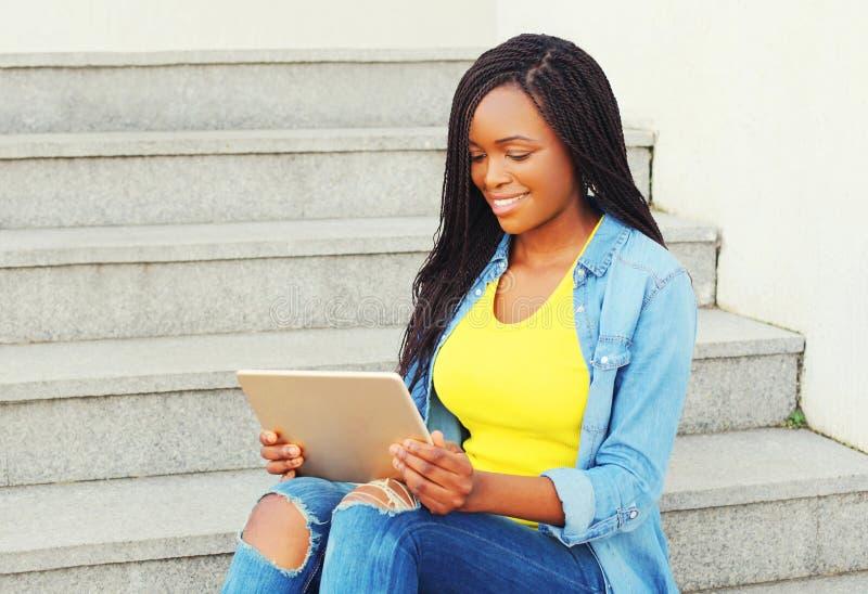 Mooie jongelui die Afrikaanse vrouw glimlachen die de computerzitting van tabletpc in stad gebruiken royalty-vrije stock foto