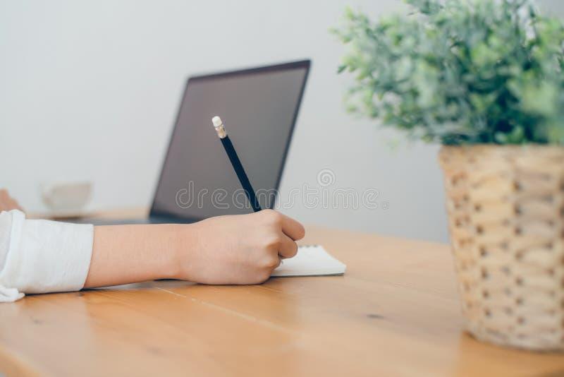Mooie jongelui die Aziatische vrouw glimlachen die aan laptop werken terwijl sitt royalty-vrije stock foto's