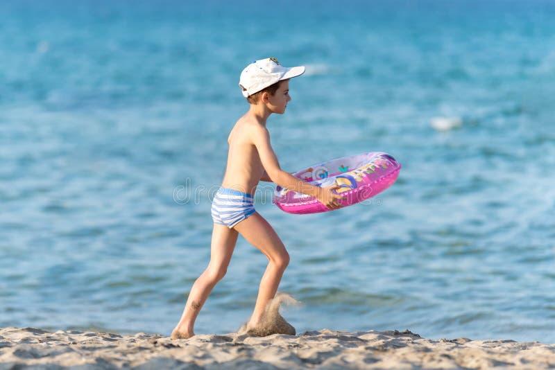 Mooie jongen die op zand met een reddingsboei lopen royalty-vrije stock afbeeldingen