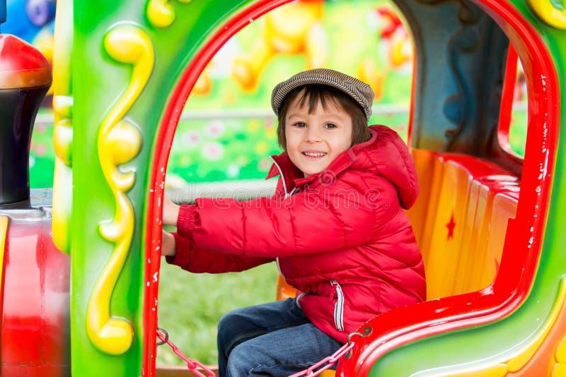 Mooie jongen die pret op de rit hebben bij het pretpark royalty-vrije stock afbeeldingen
