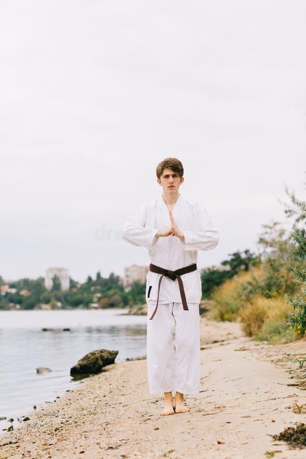 Mooie jongen in witte karatekimono op de strandachtergrond Het concept van de judopraktijk De ruimte van het exemplaar stock foto's