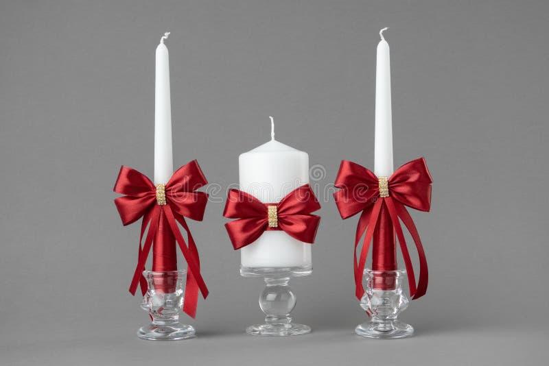 Mooie kaarsen die met rode bogen worden verfraaid stock foto