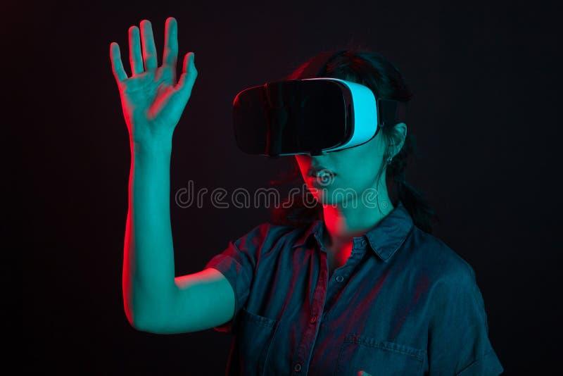 Mooie Kaukasische jonge vrouwen speelspelen die virtuele werkelijkheidshelm in studio met creatieve verlichting gebruiken stock afbeeldingen