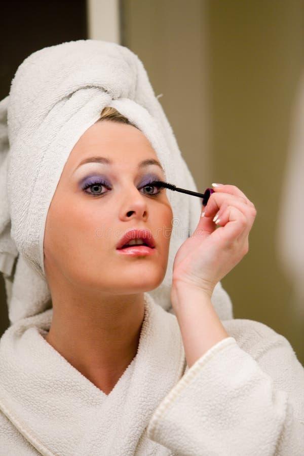 Mooie Kaukasische vrouw die make-up doet stock foto