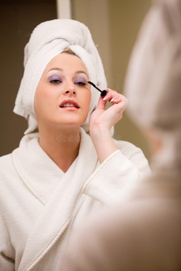 Mooie Kaukasische vrouw die make-up doet stock afbeelding