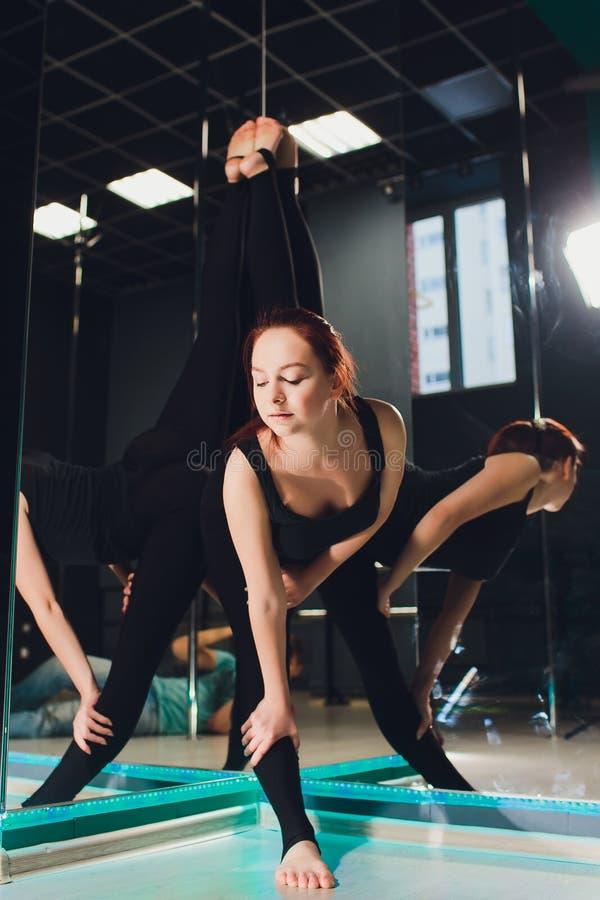 Mooie Kaukasische vrouwenturner met lang haar en slank lichaam die uitrekkende oefening doen dichtbij spiegel in dansklasse stock afbeelding