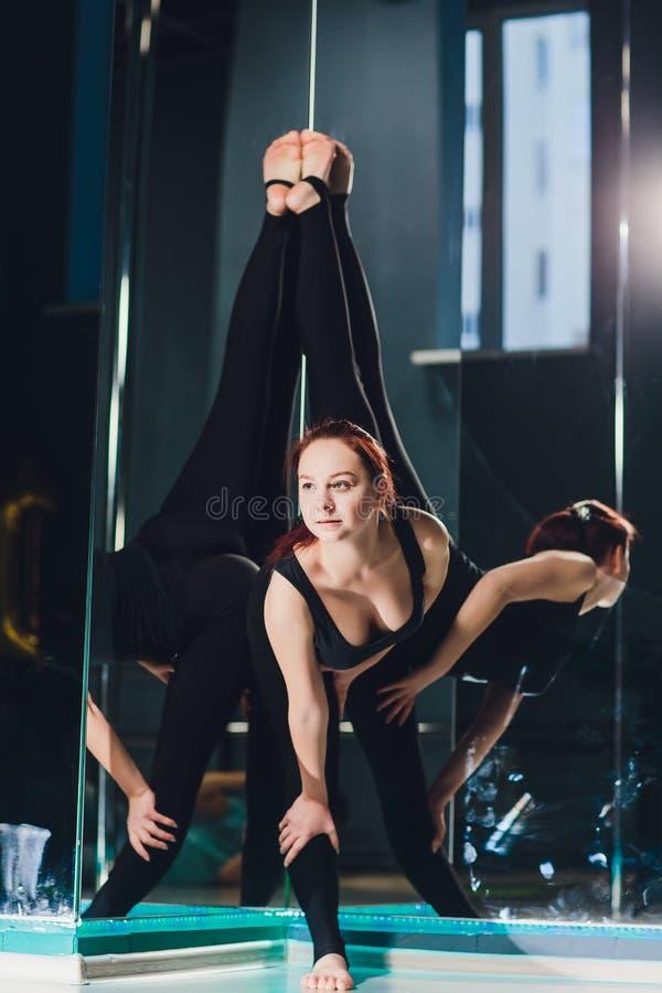 Mooie Kaukasische vrouwenturner met lang haar en slank lichaam die uitrekkende oefening doen dichtbij spiegel in dansklasse stock foto's