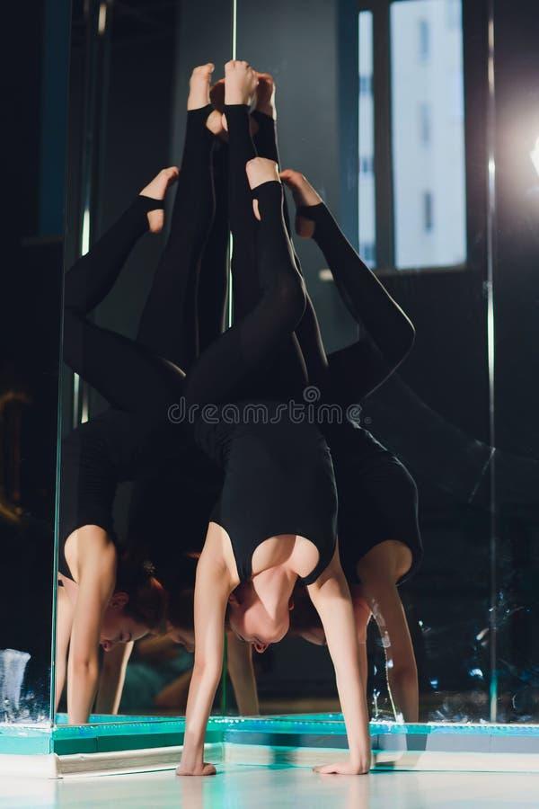 Mooie Kaukasische vrouwenturner met lang haar en slank lichaam die uitrekkende oefening doen dichtbij spiegel in dansklasse royalty-vrije stock fotografie