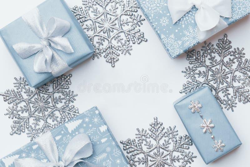 Mooie Kerstmisgiften en zilveren die sneeuwvlokken op witte achtergrond worden geïsoleerd Dozen van pastelkleur de blauwe gekleur royalty-vrije stock afbeelding