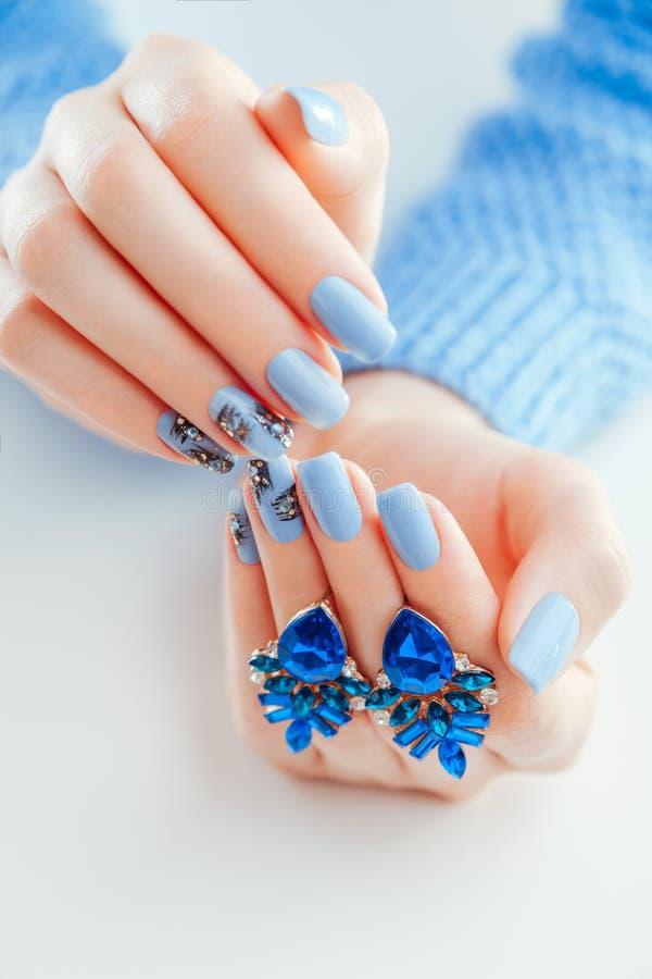 Mooie Kerstmismanicure met oorringen Blauwe spijkers met zwart ontwerp en bergkristallen stock afbeeldingen