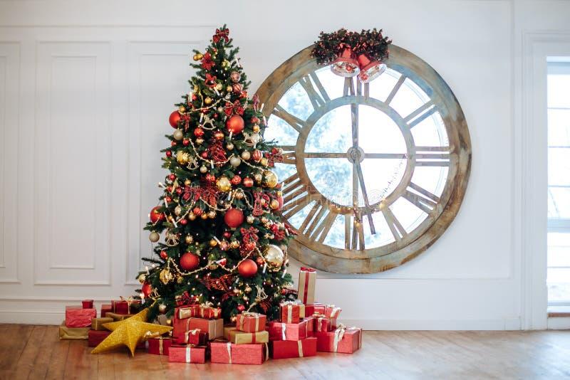 Mooie Kerstmiswoonkamer met verfraaide Kerstboom, giften voor whatemuur Nieuwe jaarboom met rood en gouden decor royalty-vrije stock fotografie