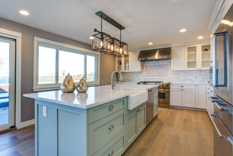 Mooie keukenruimte met groene eiland en landbouwbedrijfgootsteen stock foto