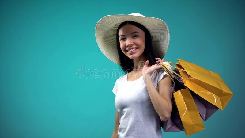 Mooie klant die in grote hoed met document zakken camera en het glimlachen bekijken stock foto