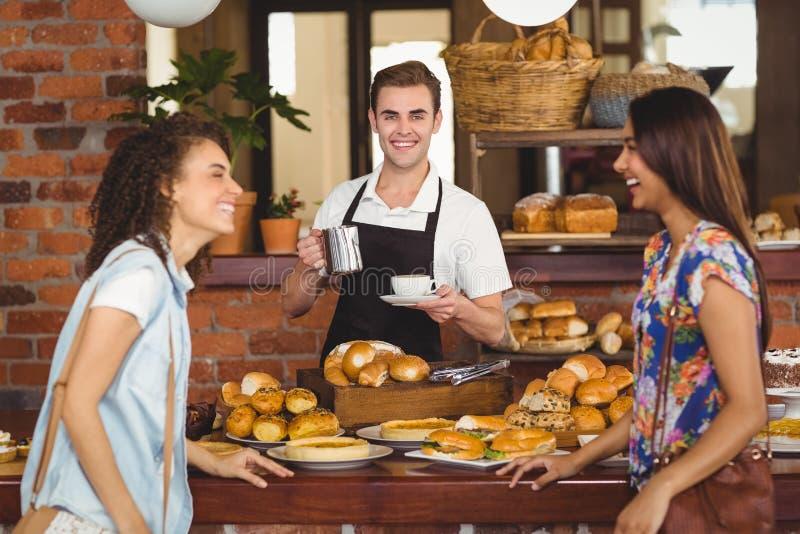 Mooie klanten die voor het glimlachen barista lachen royalty-vrije stock afbeeldingen