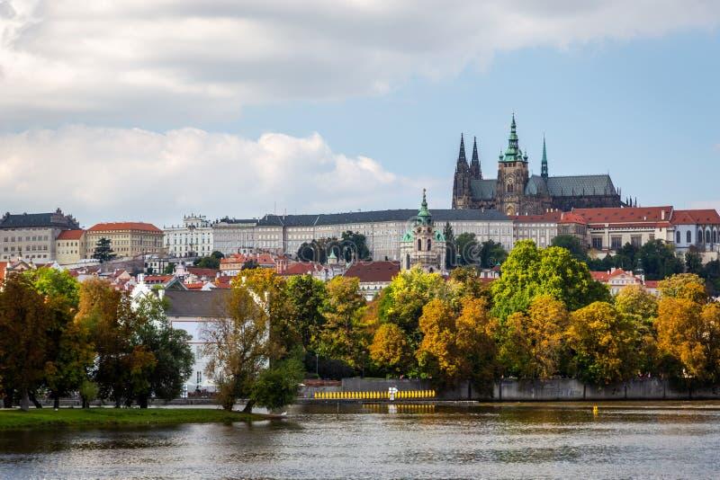 Mooie kleurrijke die de herfstcityscape mening van het kasteel van Praag van de rivier wordt gezien stock afbeeldingen
