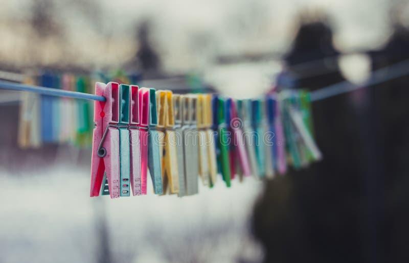 Mooie kleurrijke wasknijpers op de waslijn met sneeuw op achtergrond in de winter royalty-vrije stock afbeeldingen