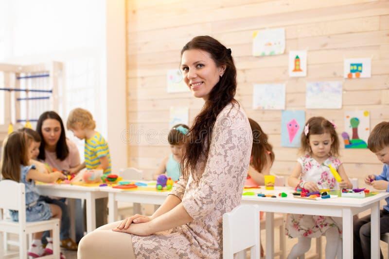 Mooie kleuterschoolleraar in klaslokaal met jonge geitjes royalty-vrije stock afbeelding