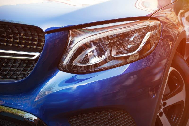 Mooie koplamp van blauwe auto door close-up in een zonnige dag Soort met aan de kant royalty-vrije stock afbeeldingen