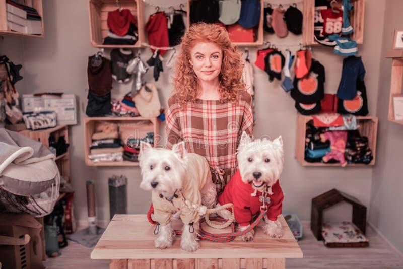Mooie krullende vrouw met koperachtig haar die zich dichtbij haar leuke honden bevinden royalty-vrije stock afbeeldingen