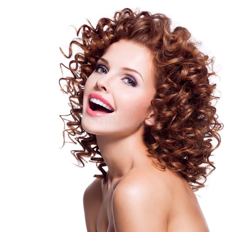 Mooie lachende vrouw met donkerbruin krullend haar stock afbeelding