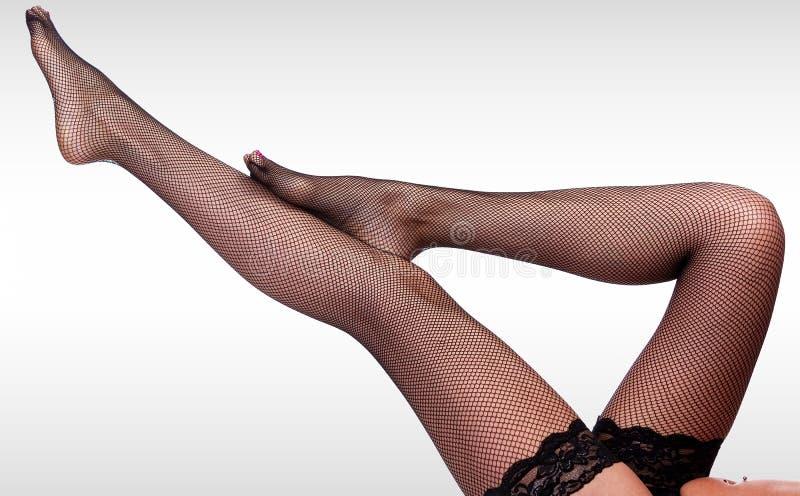 Mooie lange vrouwen` s benen in zwarte netto nylonkousen stock afbeeldingen
