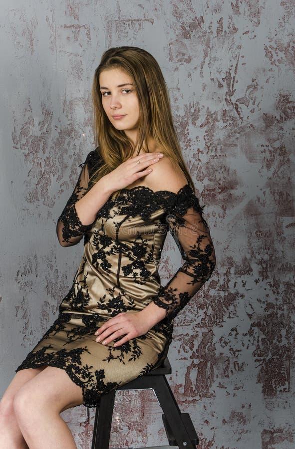 Mooie langharige jonge blondevrouw met een slank cijfer in een gouden en zwarte minikleding royalty-vrije stock foto's