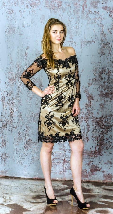 Mooie langharige jonge blondevrouw met een slank cijfer in een gouden en zwarte minikleding royalty-vrije stock afbeelding