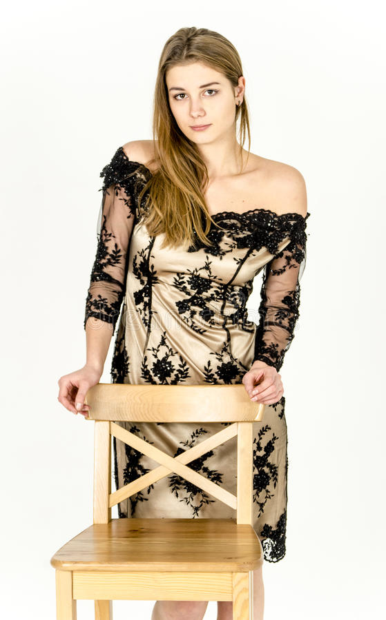 Mooie langharige jonge blondevrouw met een slank cijfer in een gouden en zwarte minikleding stock fotografie