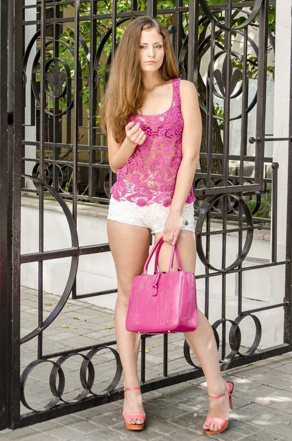 Mooie langharige vrouw in een transparante roze betoverende stijl van kleding die onderaan de straat lopen stock foto