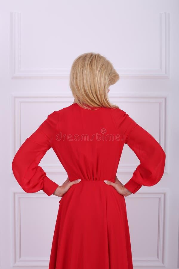 Mooie langharige vrouw in rode kleding stock afbeelding