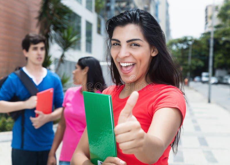 Mooie Latijnse vrouwelijke student die duim met de Kaukasische mens en inheems meisje tonen royalty-vrije stock foto's