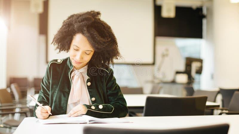 Mooie Latijnse vrouwelijke student met krullende studie in klassenruimte royalty-vrije stock fotografie