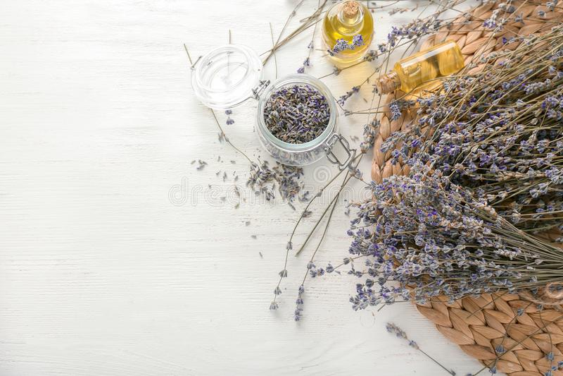 Mooie lavendelbloemen met flessen etherische olie op witte lijst royalty-vrije stock afbeeldingen