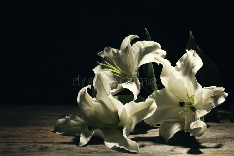 Mooie lelies op donkere achtergrond met ruimte voor tekst stock foto's
