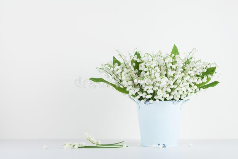 Mooie lelietje-van-dalenbloemen in blauwe vaas op witte achtergrond Het boeket van het de lentearoma royalty-vrije stock foto