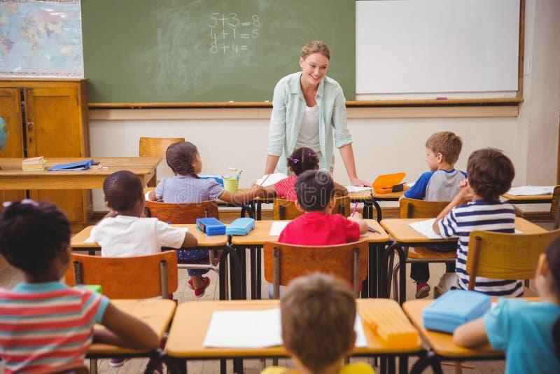 Mooie leraar die aan de jonge leerlingen in klaslokaal spreken stock foto