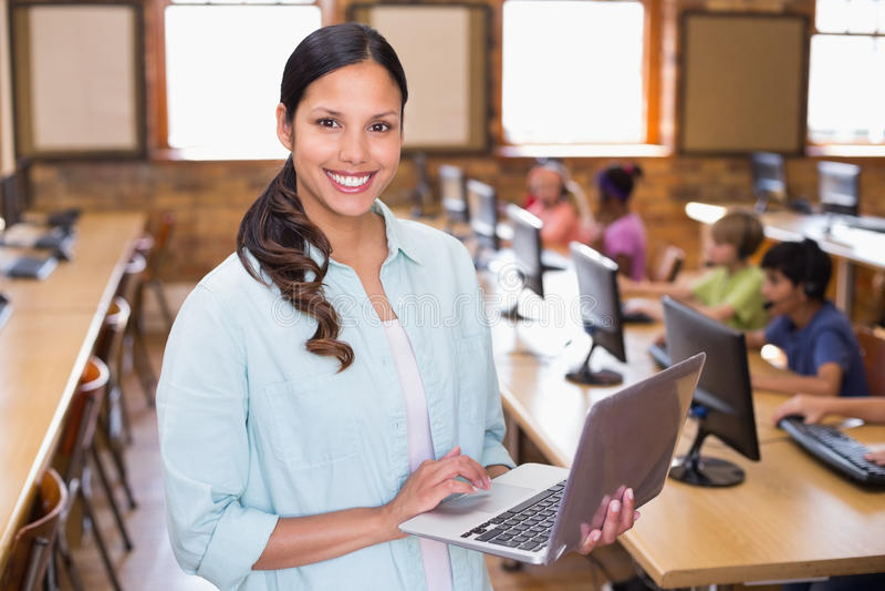 Mooie leraar die laptop in computerklasse met behulp van stock afbeeldingen