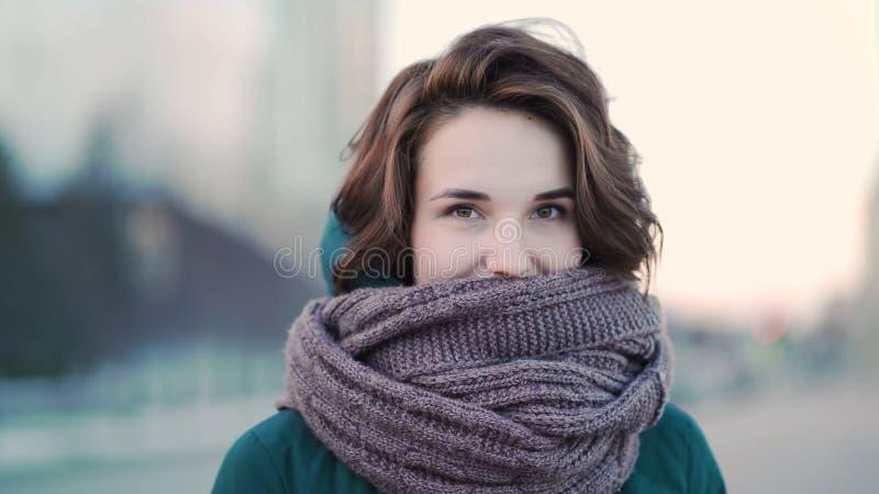 Mooie leuke jonge vrouw met een sjaal op de straat op achtergrondstad Stedelijke stijl stock foto