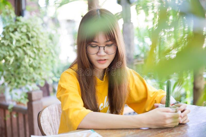 Mooie leuke portret Aziatische tiener die groene installatie houden stock afbeeldingen