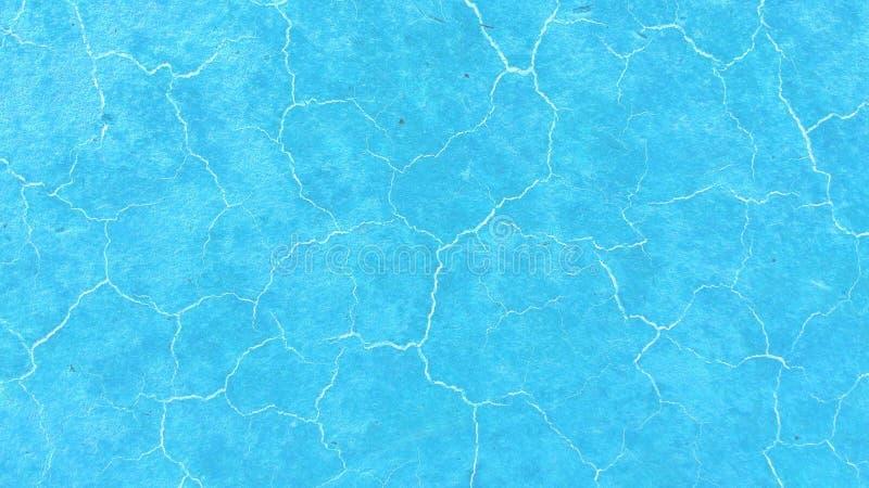 Mooie lichtblauwe achtergrond Lichte barsten op de oppervlakte Textuur van oude verf Blauwe gronddroogte gebarsten textuur stock fotografie