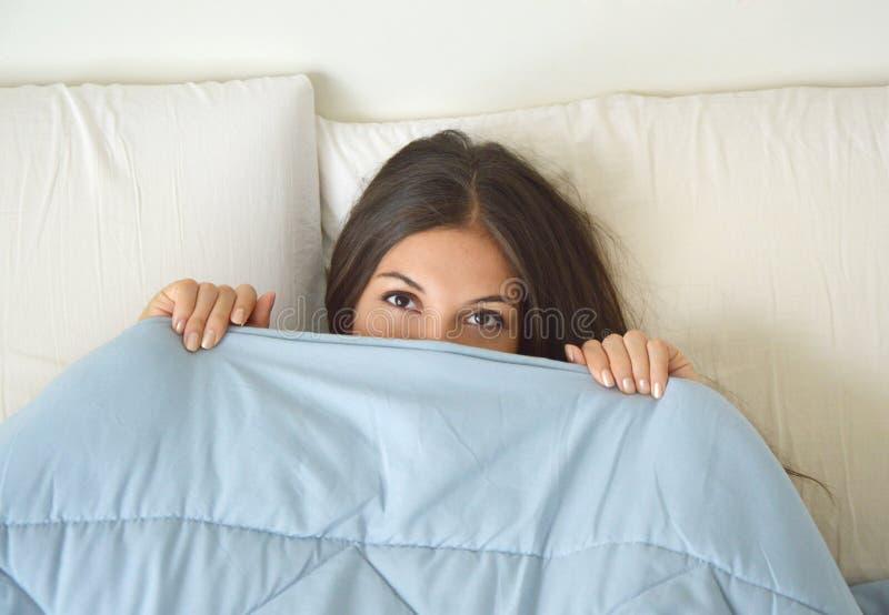 Mooie luie jonge vrouw die in het bed en het slapen liggen Het tienermeisje met open ogen behandelt haar gezicht met deken in mor royalty-vrije stock fotografie