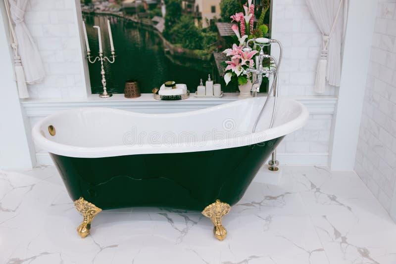 Mooie luxe uitstekende lege badkuip dichtbij groot venster in badkamersinterio, vrije ruimte stock fotografie