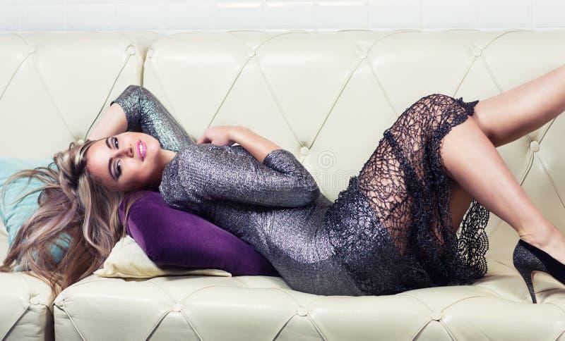 Mooie luxueuze vrouw die op een laag liggen royalty-vrije stock afbeelding