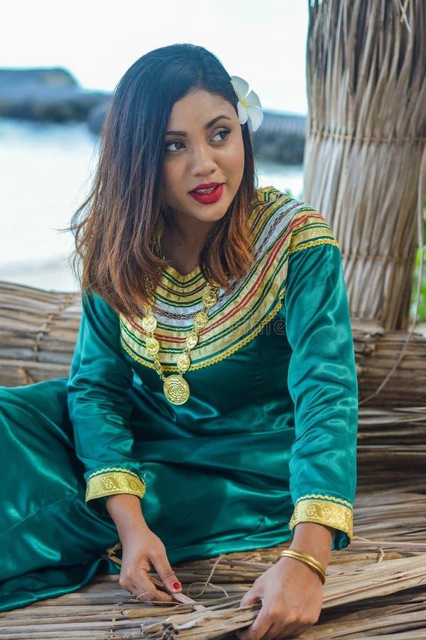 Mooie maldivian vrouw die in traditionele nationale kleding dakbladen maken stock afbeeldingen