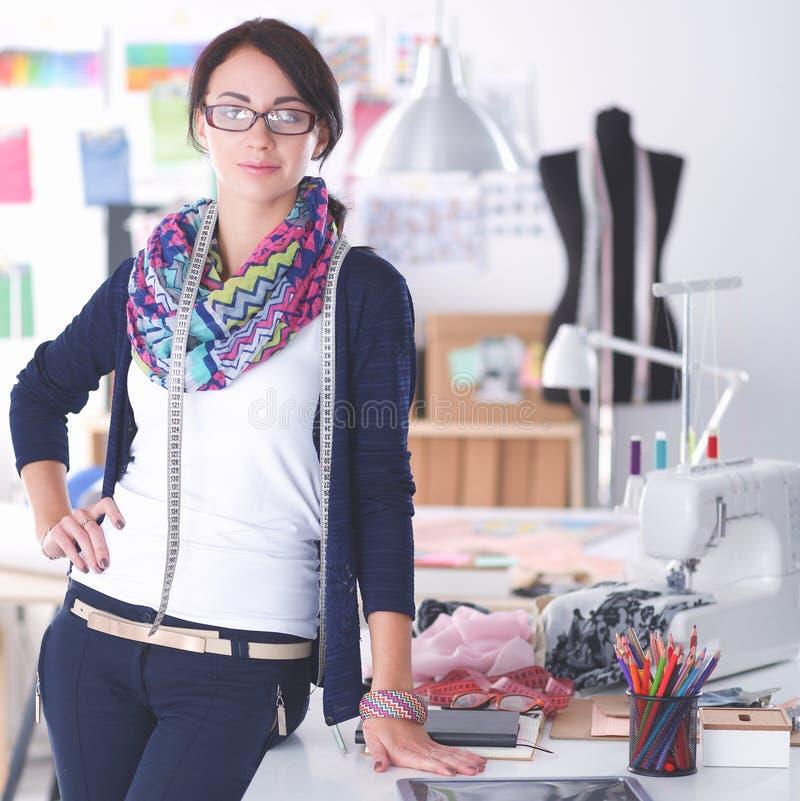 Mooie manierontwerper die zich dichtbij bureau in studio bevinden stock afbeelding